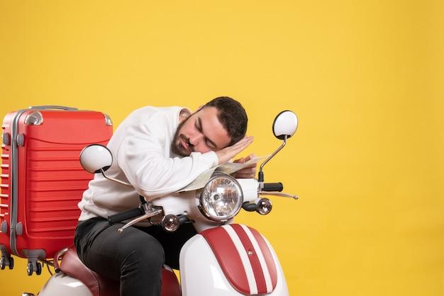 Reisekonzept mit verschlafenem kerl, der auf dem motorrad mit koffer darauf auf gelb sitzt