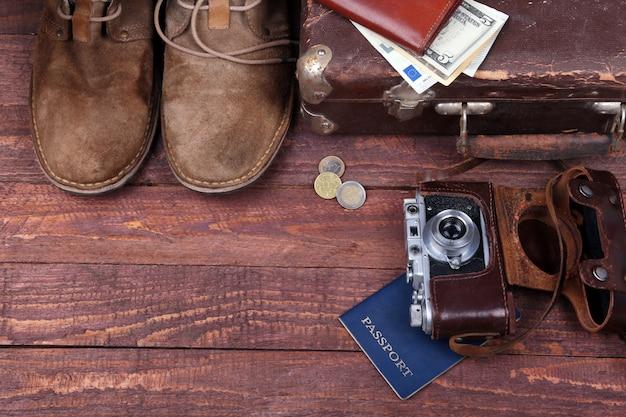Reisekonzept mit weinlesekoffer, sonnenbrille, alter kamera, velourslederstiefeln, fall für geld und pass auf bretterboden.