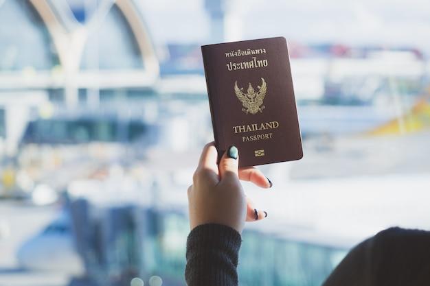 Reisekonzept nahaufnahme der frauenhand thailändischen pass bereit zum verschalen halten.