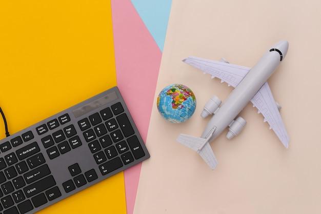 Reisekonzept. pc-tastatur und flugzeug, globus auf farbigem tisch