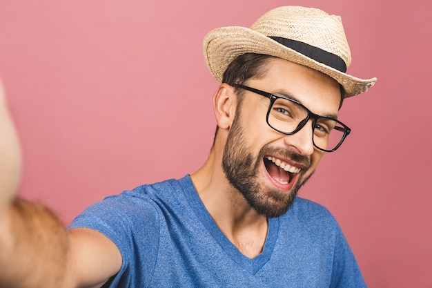 Reisekonzept. porträt des fröhlichen jungen mannes im strohhut, der selfie mit smartphone lokalisiert über rosa hintergrund nimmt.