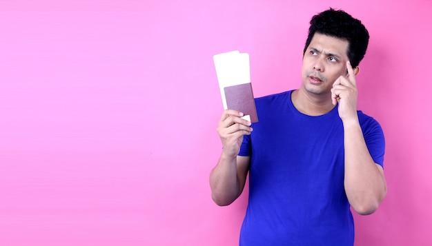 Reisekonzept. porträt des hübschen jungen asiatischen mannes, der pass hält und über etwas nachdenkt. isoliert auf isoliert auf rosa wand.