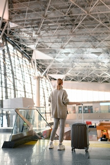 Reisekonzept. reisende frau, die mit einem gepäck am flughafenterminal geht.