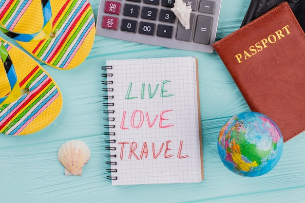 Reisekonzept von oben mit pass, sandale, muschel auf blauem hintergrund. live-liebesreise auf dem notizblock.