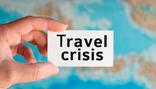 Reisekrise - text auf einem weißen blatt in der hand gegen die oberfläche der atlaskarte