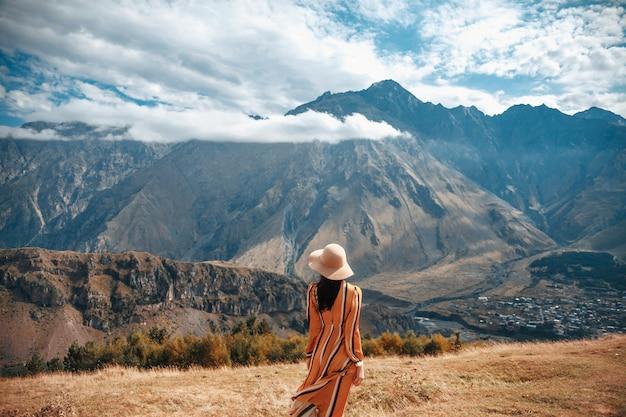 Reiselebensstil-frauentourist im freien, der auf bergen und bewölktem himmel aufwirft.