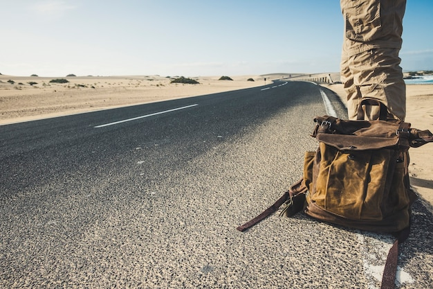 Reiseleute und abenteuerlebensstilkonzept mit nahaufnahme des mannes, der auf dem langen weg mit dem trendigen rucksack steht, der auf ein auto wartet, um die reise zu teilen