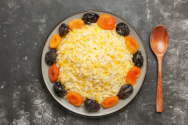 Reiselöffel der oberen nahansicht der appetitlichen getrockneten früchte und des reises in der platte auf dem tisch