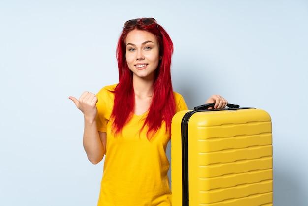 Reisemädchen, das einen koffer auf blauer wand mit daumen hoch geste und lächeln hält
