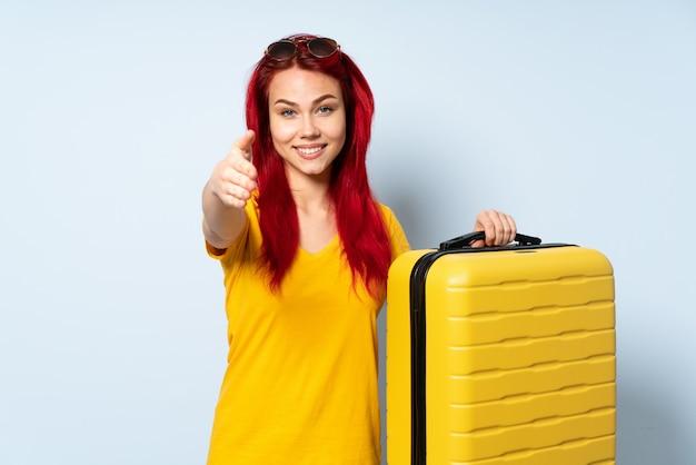 Reisemädchen, das einen koffer hält, der auf blauer wand lokalisiert wird, die hände für das schließen eines guten geschäfts schüttelt