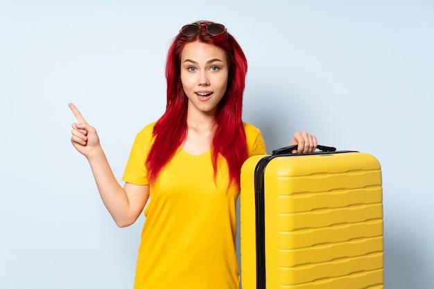 Reisemädchen, das einen koffer lokalisiert auf blauem hintergrund hält, überrascht und finger zur seite zeigend