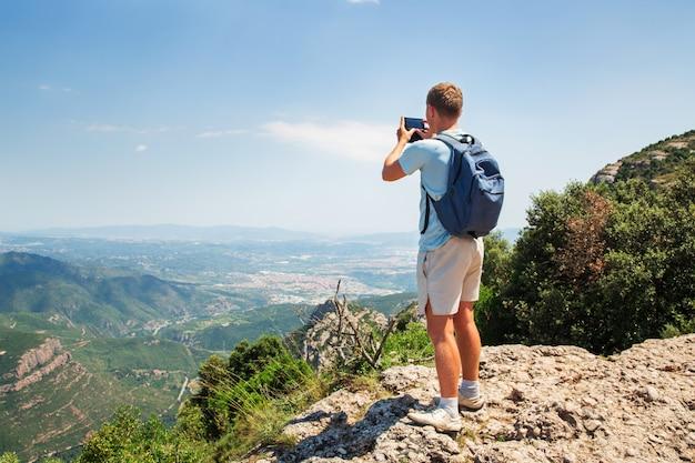 Reisemann mit rucksackstellung machen ein foto durch sonnigen tag des smartphone mountians kopienraum