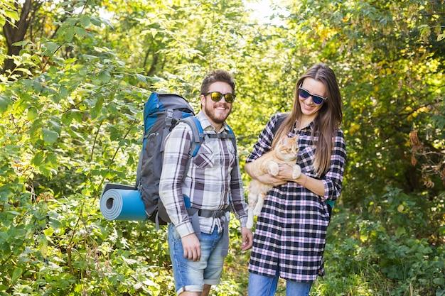 Reisen, abenteuer, wanderung, tourismus und naturkonzept - touristenpaar mit katze, die im wald spazieren geht