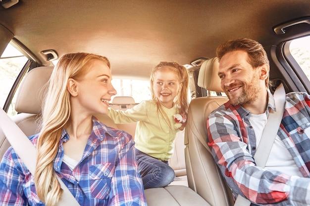 Reisen bedeutet, eine lächelnde familie zu leben, die im auto sitzt und die familienstraße fährt