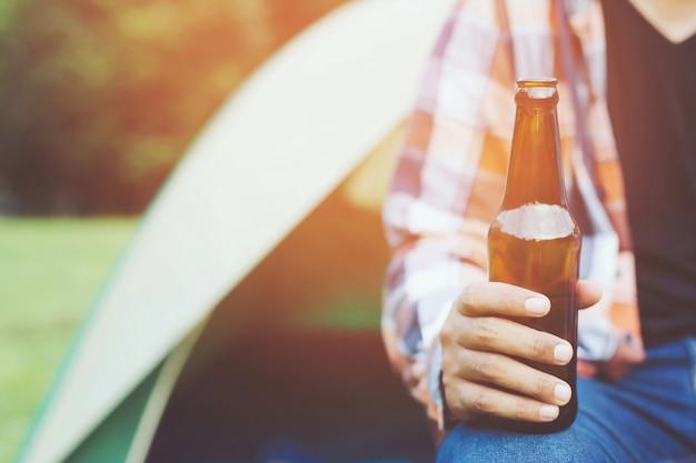 Reisen drei junge freunde, die zusammen spaß haben entspannen sie sich im wandercamp und trinken sie bier cheers flaschen und genießen. urlaub camping camping abenteuer konzept.