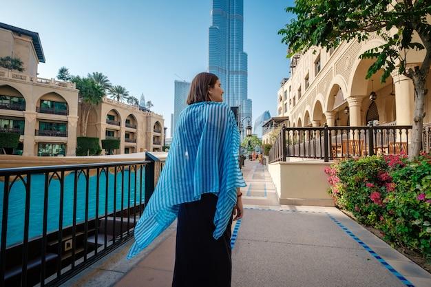 Reisen in den vereinigten arabischen emiraten genießen. junge frau im kleid gehend auf dubai im stadtzentrum gelegen.