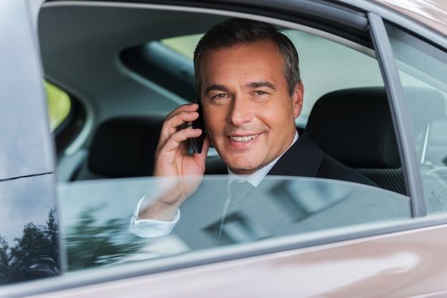 Reisen mit komfort. glücklicher reifer geschäftsmann, der auf dem handy spricht und lächelt, während er auf dem rücksitz eines autos sitzt