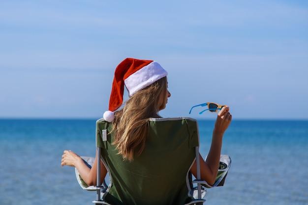 Reisen sie am silvesterabend am strand auf dem seeweg. mädchen in weihnachtsmütze nimmt ein sonnenbad in der sonne.
