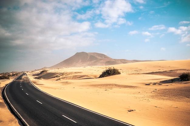 Reisen sie auf dem straßenkonzept mit einer langen asphaltstraße inmitten der sandwüste und der berge der dünen für abenteuer und alternative landschaftliche orte für urlaubs- oder abenteuer-lifestyle-erlebnisse