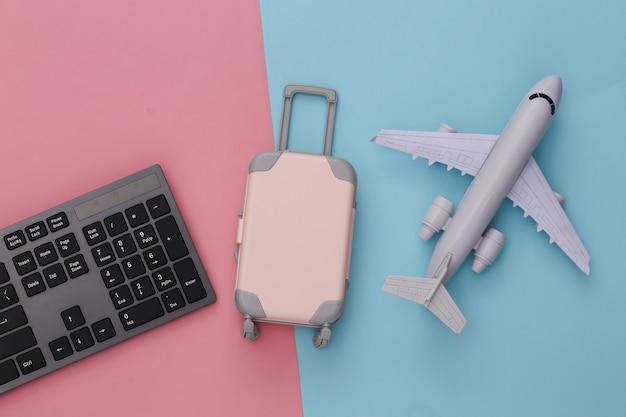 Reisen sie flach. pc-tastatur und mini-reisegepäck, flugzeug auf rosa blau