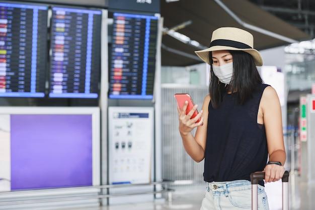 Reisen sie neu normal unter covid-19-virus-konzept, glückliche reisende asiatische frau mit maske und gepäck unter verwendung des mobiltelefons und sitzen sozialer distanzierender stuhl im terminalflughafen, thailand