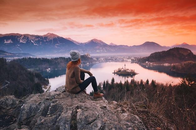 Reisen sie slowenien, europa. frau, die auf bleder see mit insel, schloss und alpenberg im hintergrund schaut. ansicht von oben. bled lake eine der erstaunlichsten touristenattraktionen. sonnenuntergang winter naturlandschaft.