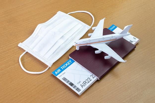 Reisen sie während der covid-19-pandemie. flugzeugmodell mit gesichtsmaske, flugticket und reisepass. bereit für den urlaub.
