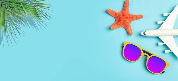 Reisen sommer hintergrund sonnenbrille palme tropische blätter flugzeug- und strandzubehör auf einem farbigen...