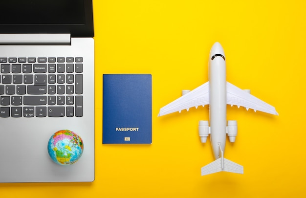 Reisen stillleben. online-buchung. auswanderung. laptop, globus, flugzeug und reisepass. touristisches zubehör auf gelbem hintergrund. draufsicht. flach liegen