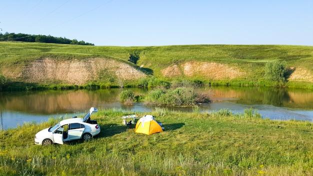 Reisen, tourismus, camping zelt am flussufer. zelt und lagerfeuer am ufer von flüssen, seen