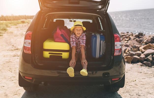 Reisen, tourismus - mädchen mit taschen bereit für die reise für die sommerferien. kind geht auf abenteuer. autofahrkonzept