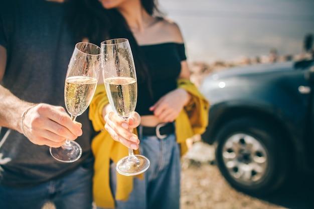 Reisen, tourismus - mann und frau trinken champagner in der nähe des wassers an einem tragbaren klapptisch. picknick am wasser. paar geht auf abenteuer. autofahrkonzept.