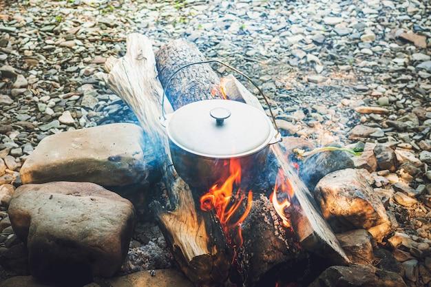 Reisen, tourismus, picknickkochen, kochen in einem kessel am feuer, kochtopf am lagerfeuer.