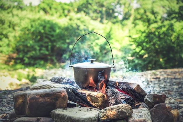 Reisen, tourismus, picknickkochen, kochen in einem kessel am feuer.