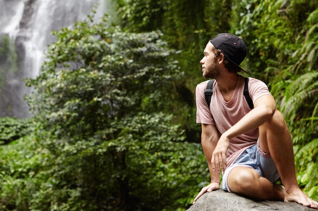 Reisen und abenteuer. hübscher junger barfuß männlicher wanderer mit rucksack, der allein auf großem stein entspannt und zurückblickt