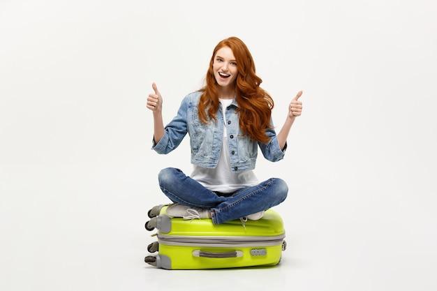 Reisen und lifestyle-konzept. junge aufgeregte kaukasische frau, die auf dem gepäckkoffer sitzt und sich daumen zeigt. getrennt auf weiß. bereit für den urlaub.