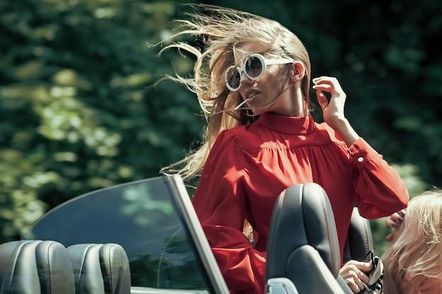 Reisen und sommerferien modernes leben luxusstadt glamour geschäftsreise glückliches mädchen fahrer geschäftsfrau oder hübsche frau im cabrio auto sexy frau fahren auto mode schönheit