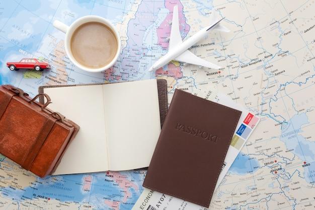 Reisen, urlaub, tourismus - nahaufnahme notizbuch, koffer, spielzeugflugzeug auf karte.