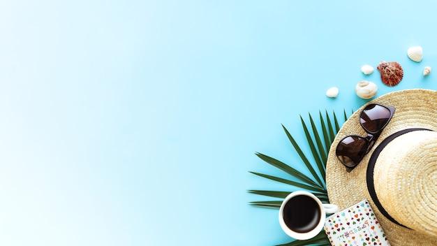 Reisen, urlaubskonzept. hut mit verschiedenen muscheln, grünem palmblatt, reisepass, brille und tasse kaffee auf blauem himmelshintergrund. reisen in warme länder. banner mit kopienraum für text