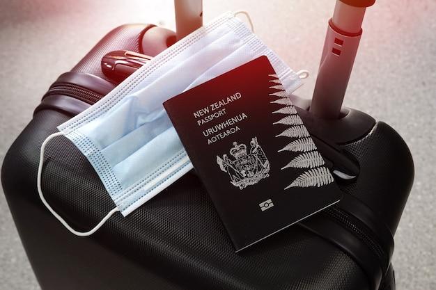 Reisen während der covid-19-pandemie. neuseeländischer pass und schutzmaske auf schwarzem koffer