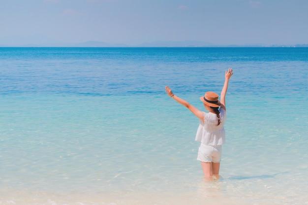 Reisend-asiatin, die auf dem strand zum sommermeer glücklich sich fühlt