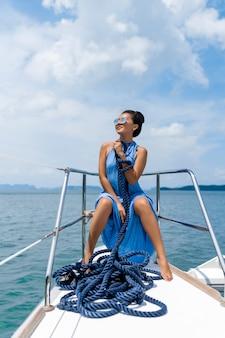 Reisend-mädchen in einem blauen kleid mit blauem seil auf yacht.