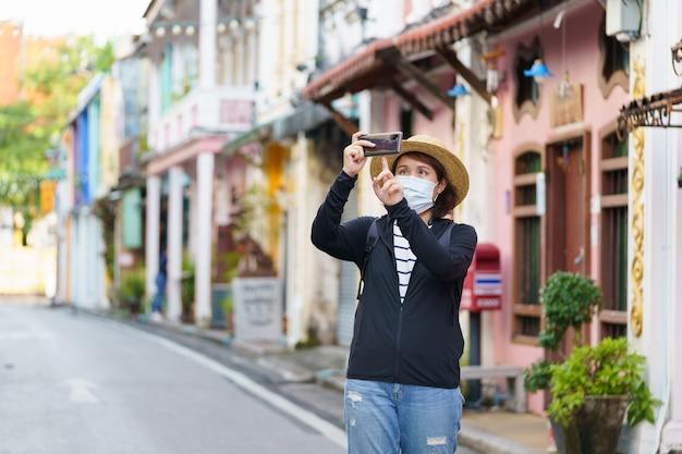 Reisende auf der straße phuket altstadt mit gebäude sino portugiesische architektur in phuket