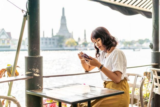 Reisende der asiatischen frau, die ihr telefon im café benutzt