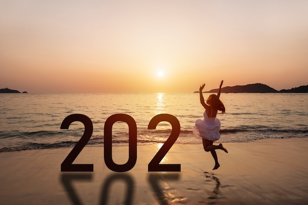 Reisende der jungen frau, die am strand springt, der neujahr am sonnenuntergang feiert