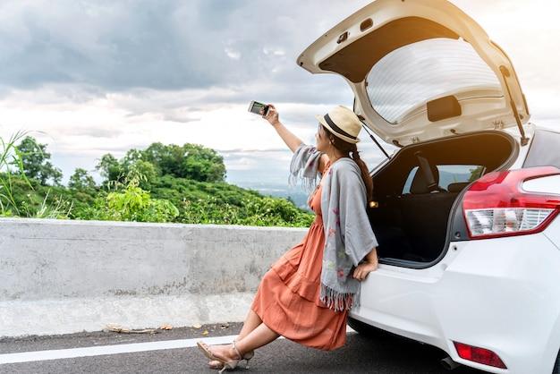 Reisende der jungen frau, die auf der rückseite des autos sitzt, während selfie foto macht