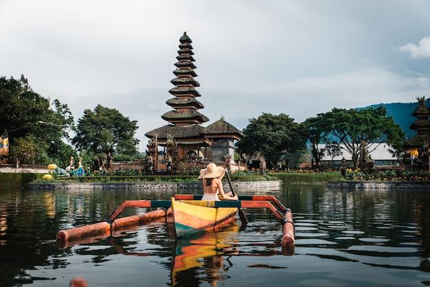 Reisende der jungen frau, die auf einem hölzernen boot bei pura ulun danu bratan paddelt