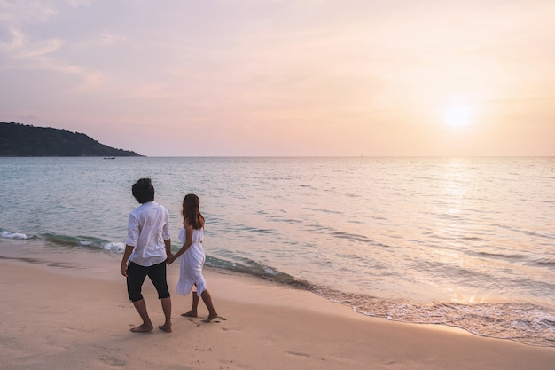 Reisende der jungen frau, die die hand des mannes hält und schönen sonnenuntergang am strand schaut