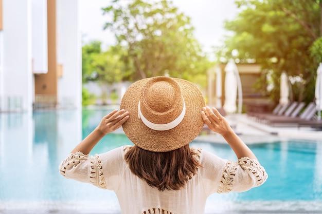 Reisende der jungen frau, die einen sommerurlaub am schwimmbad im tropischen ferienort nahe dem strand genießt