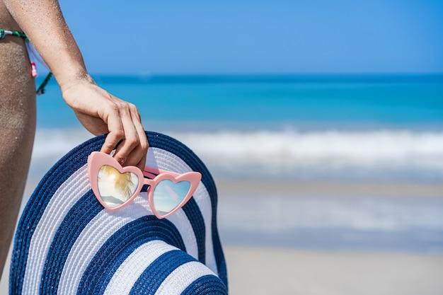 Reisende der jungen frau, die einen sommerurlaub am tropischen sandstrand genießt